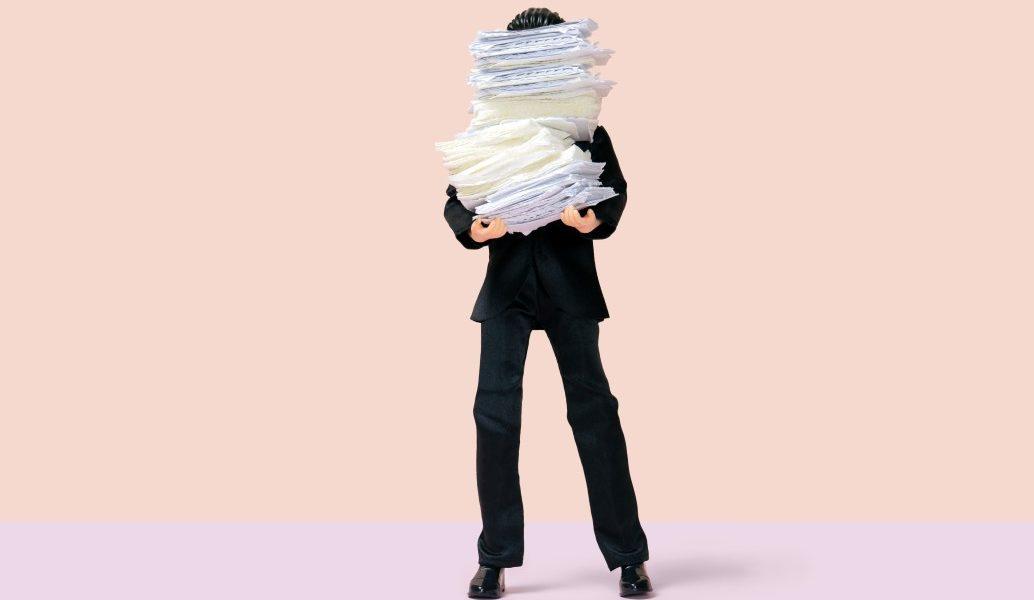 εργασιομανία άνδρας φορτωμένος από φακέλους της δουλείας