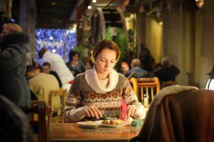 χαμογελαστή κατάθλιψη γυναίκα τρώει μόνη της σε εστιατόριο