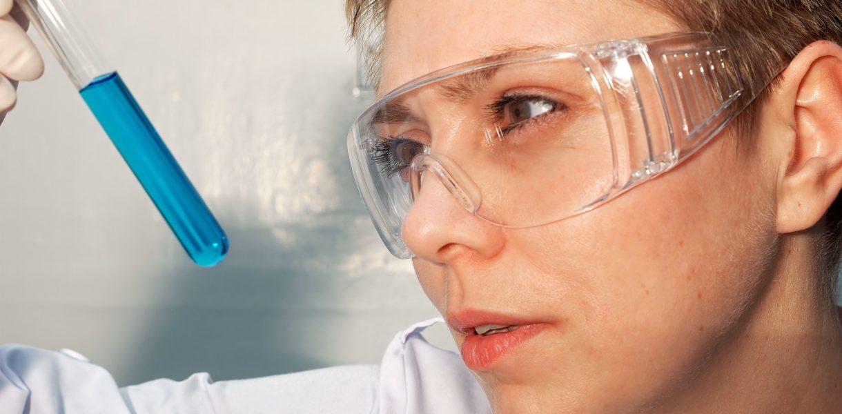 γυναίκα κοιτάζει τον εργαστηριακό σωλήνα επιστήμονες