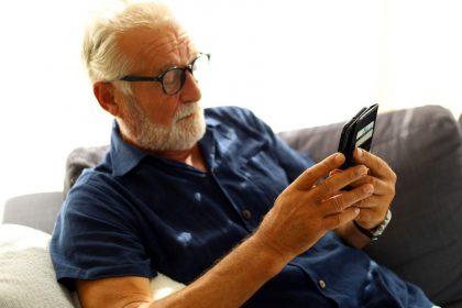 ηλικιωμένος σε κοινωνική απομόνωση με κινητό