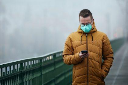 άνδρας με μάσκα σε κακοκαιρία και άνοδο των κρουσματων