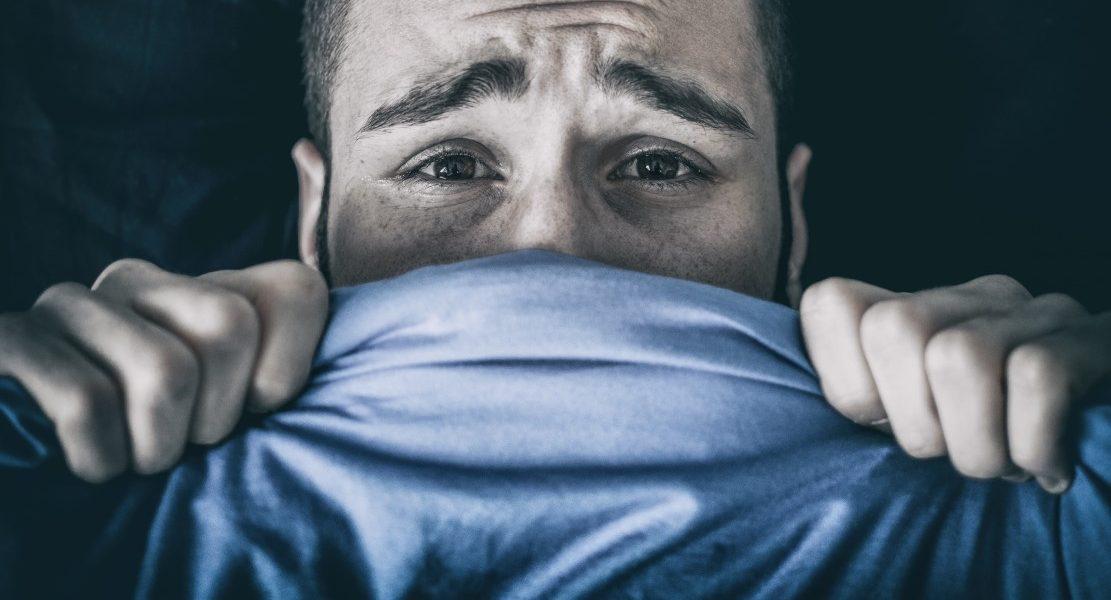 Υπνική παράλυση άντρας φοβισμένος στο κρεβάτι σκεπασμένος