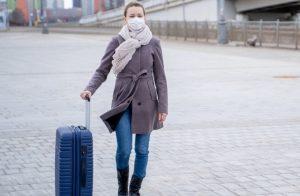 γυναίκα με βαλίτσα στο αεροδόμιο φοράει μάσκα προστασία για μετάλλαξη ιού covid19