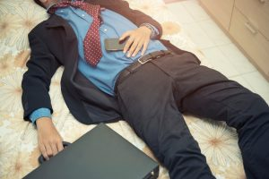 εργασιομανία άνδρας ξαπλωμένος στο πάτωμα με τα ρούχα της δουλείας