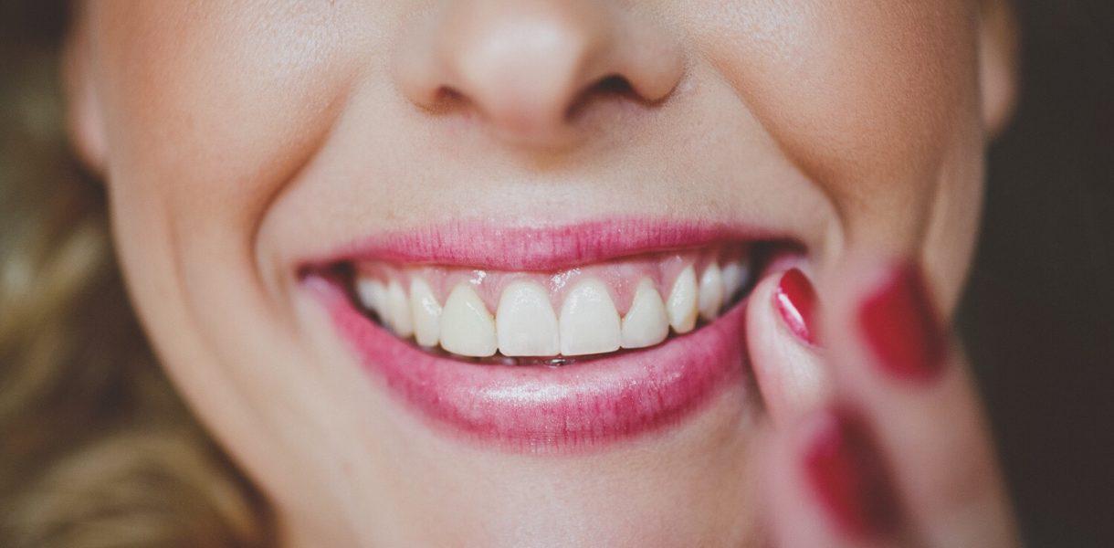 ουλίτιδα αντιμετώπιση γυναίκα στον οδοντίατρο με λευκά δόντια