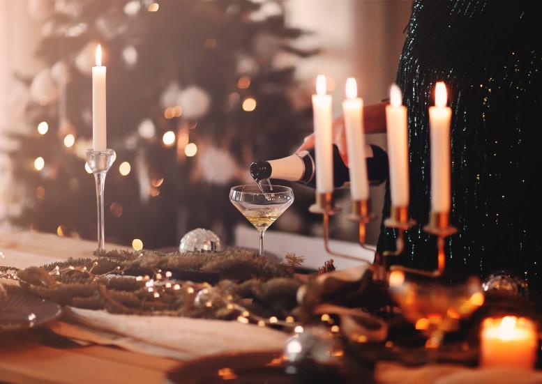 πρωτοχρονιάτικο τραπέζι γυναίκα βάζει σαμπάνια σε δείπνο πρωτοχρονιάς