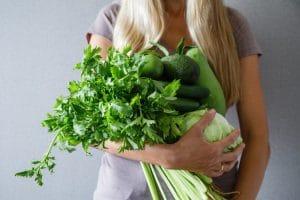 σπανάκι και πράσινα λαχανικά που κρατάει γυναίκα για ενίσχυση του αιματοκρίτη