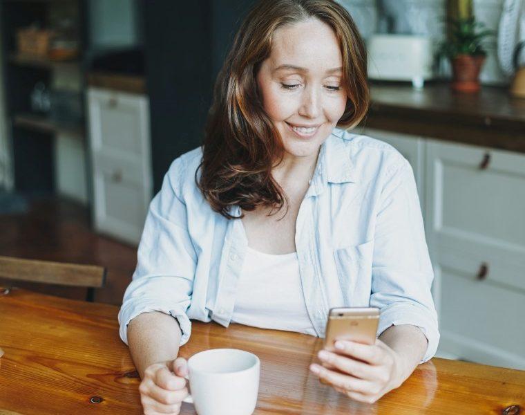 εμμηνόπαυση ορμονοθεραπεία γυναίκα κοιτάει το κινητό της και χαμογελάει