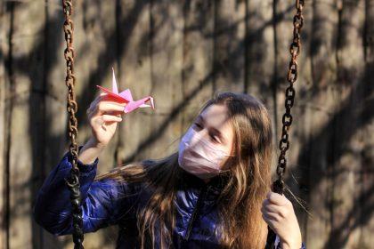 κοριτσάκι κρατάει χάρτινο οριγκάμι και κάνει κούνια