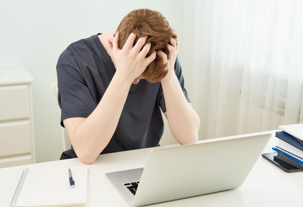άνδρας με προβλήματα ψυχικής ασθένειας κρατάει το κεφάλι του