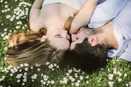 demisexual ζευγάρι είναι ξαπλωμένο στο χορτάρι και φιλιέται
