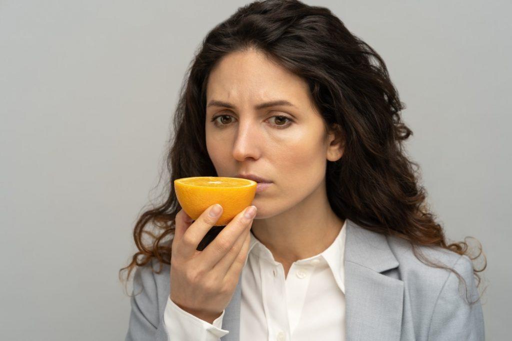 γυναίκα με ανοσμία που προσπαθεί να μυρίσει πορτοκάλι
