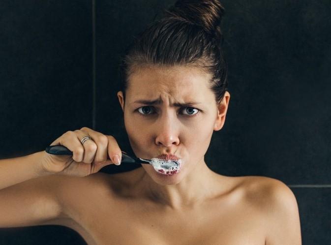 στοματική υγεία και κακή ψυχολογία γυναίκας που πλένει τα δόντια της