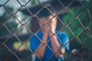 Κακοποιημένο αγόρι κλαίει πίσω από σύρματα
