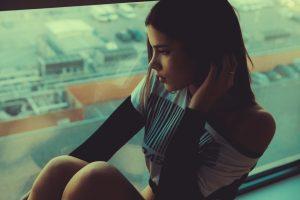 μελαγχολική κατάθλιψη γυναίκα κάθεται στο τζάμι στεναχωρημένη