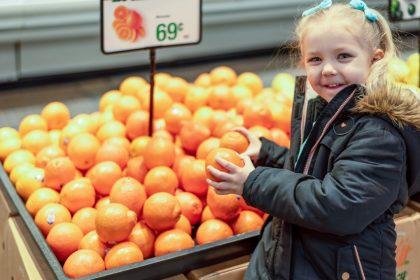 οφέλη βιταμίνης C κοριτσάκι κρατάει πορτοκάλια