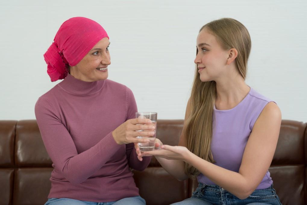 Κοπέλα προσφέρει νερό σε γυναίκα με λέμφωμα