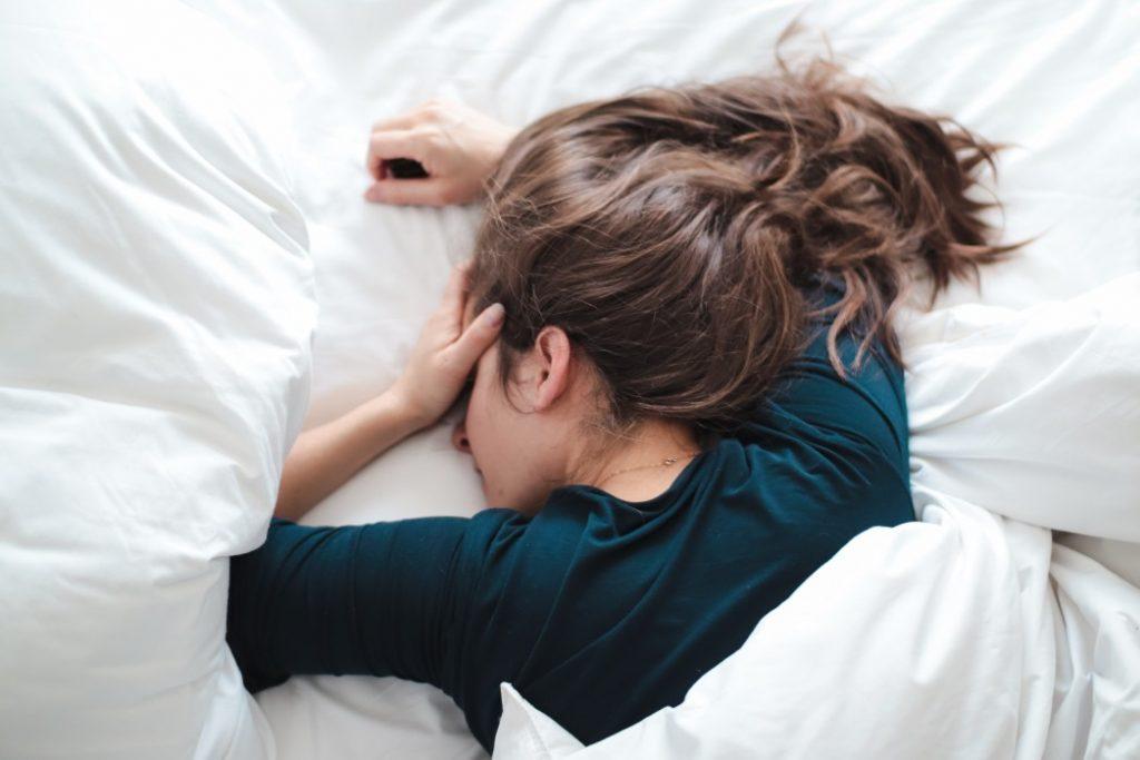 Μελαγχολική γυναίκα ξαπλωμένη στο κρεβάτι