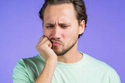 άνδρας πονάει γιατι έχει ευαίσθητα δόντια στο κρύο νερό