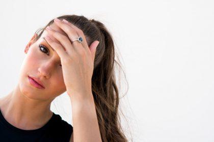 ορμονική ημικρανία περίοδο γυναίκα πιάνει το κεφάλι της που πονάει