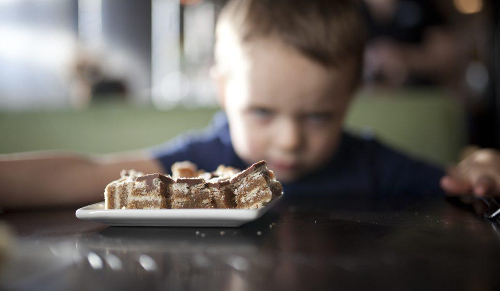θυμωμένο αγόρι θελει να φάει το γλυκό απο το πιάτο