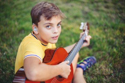 προβλήματα ακοής κωφό παιδί παίζει κιθάρα