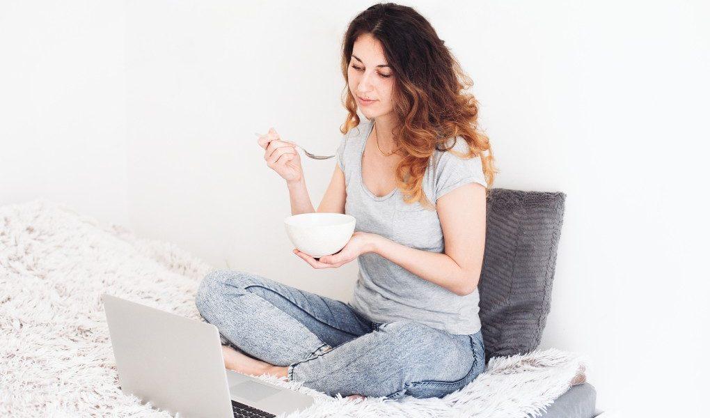 σνακ πριν τον ύπνο γυναίκα τρώει το βραδινό στο κρεββάτι