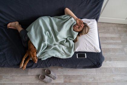 κατάθλιψη πόνοι στο σώμα κοπέλα στο κρεββάτι με σκύλο