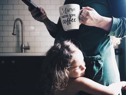 εθισμός στην καφεΐνη γυναίκα πίνει καφέ και η κόρη της αγκαλιάζει