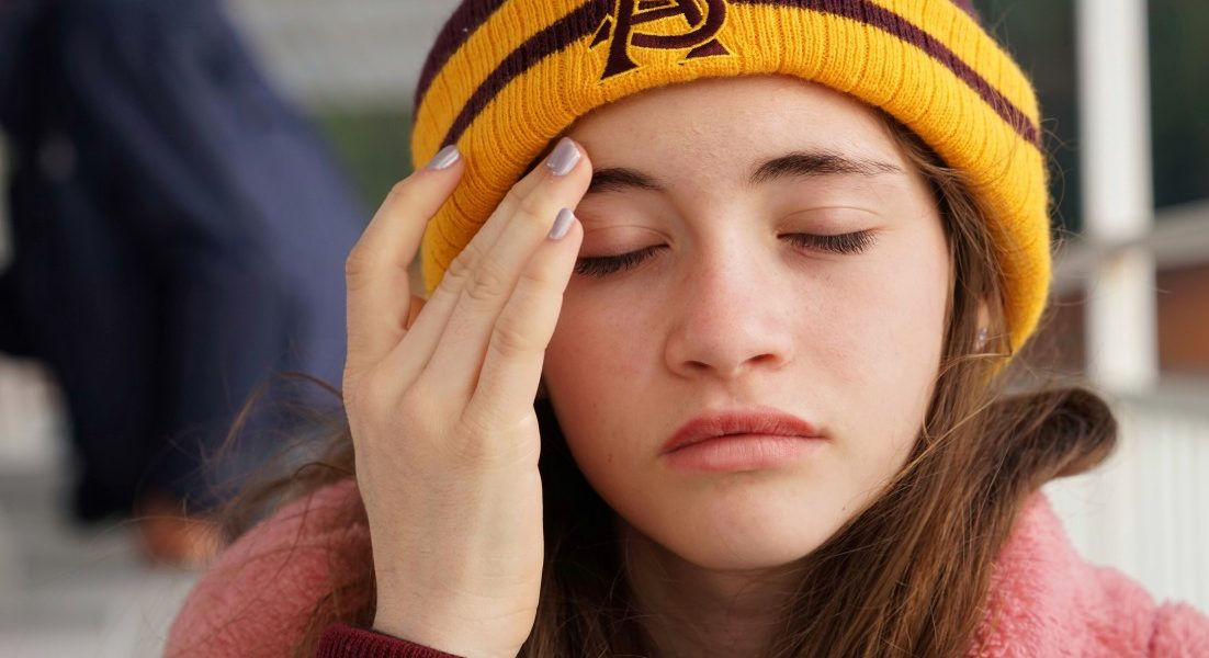 αθροιστική κεφαλαλγία κοπέλα με σκουφάκι και πονοκέφαλο