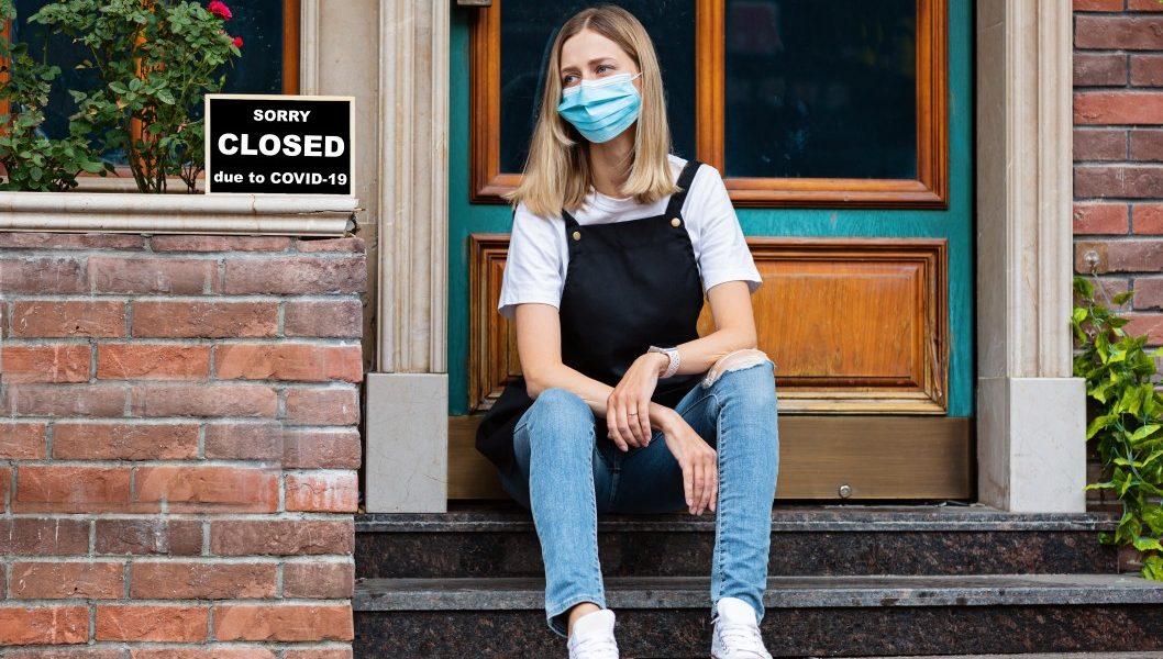 covid-19 ψυχολογικά γυναίκα κάθεται έξω από το κλειστό μαγαζί της λόγω πανδημίας