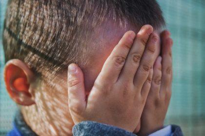 παιδική κακοποίηση παιδί κλαίει και κρύβει το πρόσωπό του