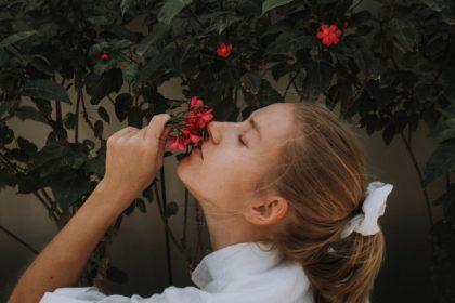 γυναίκα προσπαθεί να μυρίσει τα λουλούδια λόγω εμμένουσας ανοσμίας