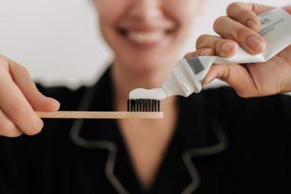 γυναίκα κρατάει οδοντόβουρτσα και διατηρεί την υγεία των ούλων