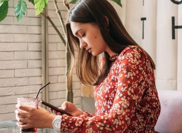 κοπέλα κοιταζει εφαρμογή γνωριμιών στο κινητό για περιστασιακό σεξ