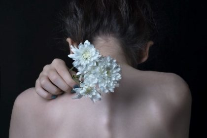 σπυράκια στην πλάτη γυναίκα κρατά λουλούδι στην πλάτη της